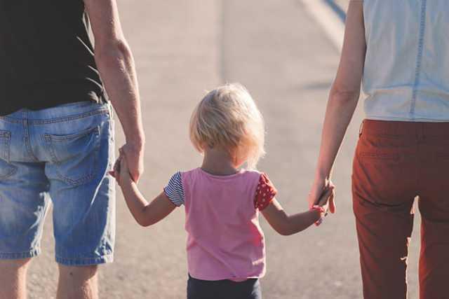 Ребенок держит за руки взрослых